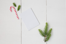 candy canes and pine boughs with blank white paper