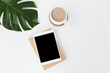 tropical leaves and iPad on a notebook