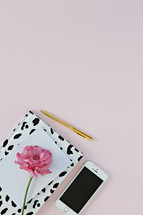 pink carnation, paper, notebook, pen, and cellphone on a pink background
