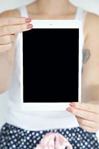 a woman holding up a blank tablet screen