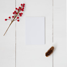 red berries, pine cone, and blank white paper