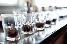 coffee beans in a row of glasses