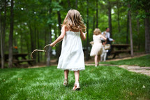 little girl running holding a stick in the park