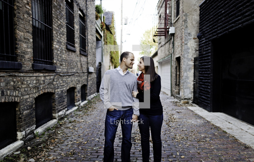 A happy couple stands in a cobble-stoned alley