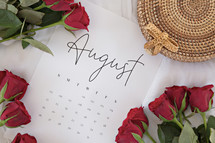 red roses on a calendar of August
