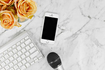 cellphone, microphone, computer keyboard, and yellow roses on a marbled background