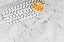 computer keyboard, and yellow roses on a marbled background