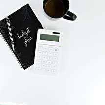 Budget plan, pen, calculator, and coffee mug