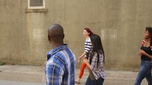 group of young adults walking in an alley