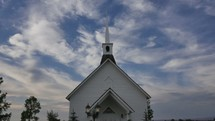 clouds over a white church with steeple