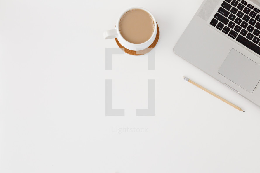 laptop computer and coffee cup on a white desk