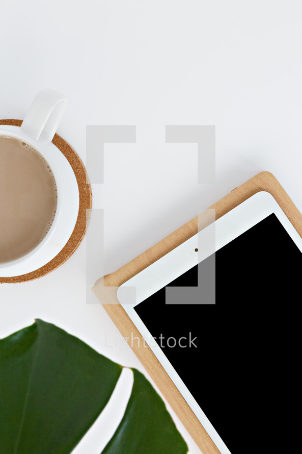 tropical plant leaf, coffee cup, iPad, and notebook on a white desk