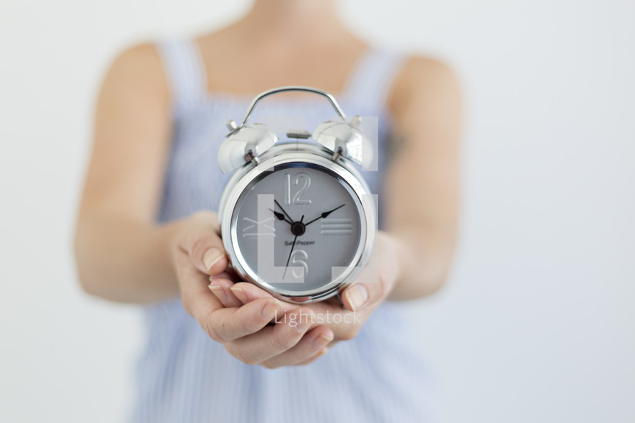 woman holding an alarm clock in cupped hands