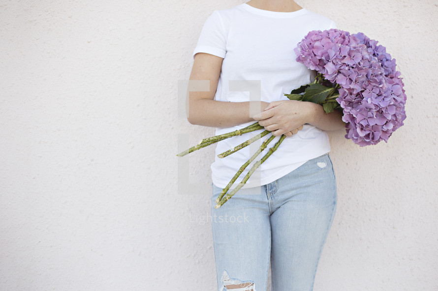 a woman holding a bouquet of hydrangeas