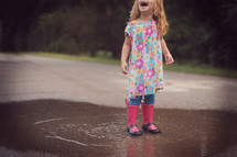 a child splashing in a puddle in rain boots
