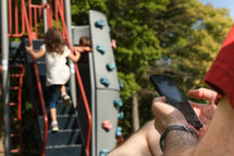 a father looking at his cellphone while kids play at a playground