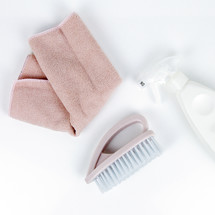 pink towel, brush, and spray bottle