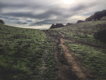 rutted path or road going through the hillside with a cloudy sky