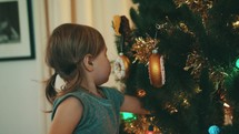 toddler girl hanging ornaments on a Christmas tree