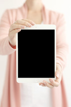 a woman holding up a tablet