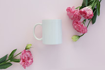 pink carnations and white coffee cup