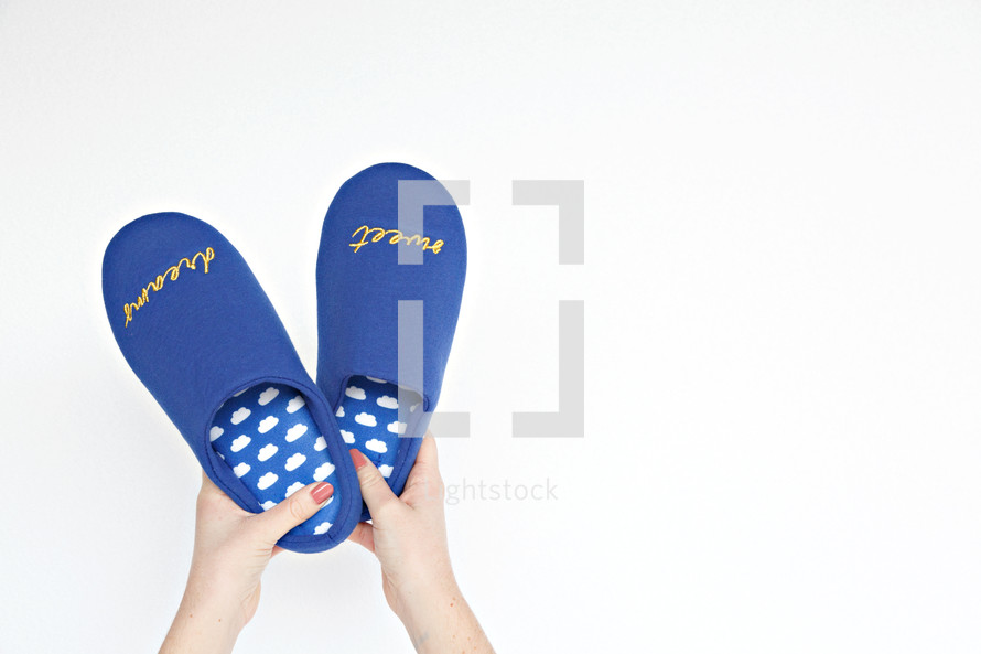 woman holding bedroom slippers