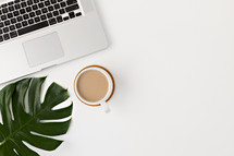 laptop computer, coffee cup, and tropical leaf on a white desk