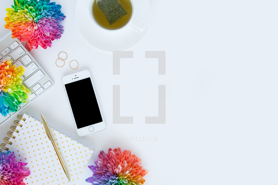 tea bag, cellphone,  tea, desk, rainbow, flowers, computer, keyboard, pen, gold,  journal, white background
