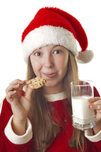 girl child in a Santa hat holding cookies and milk