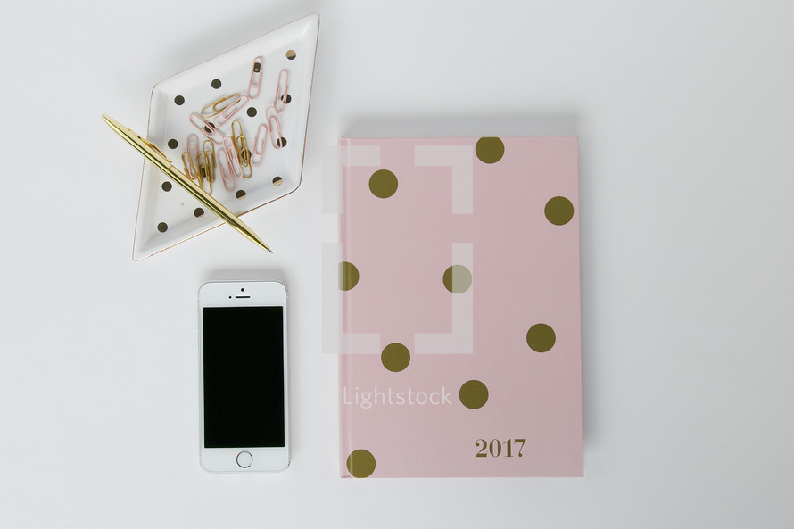 paperclips, tray, cellphone, 2017 planner on a desk