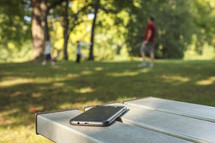 cellphone on a picnic table and a family playing at a park