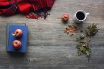 plaid blanket, apples, vintage books, and fall leaves on wood