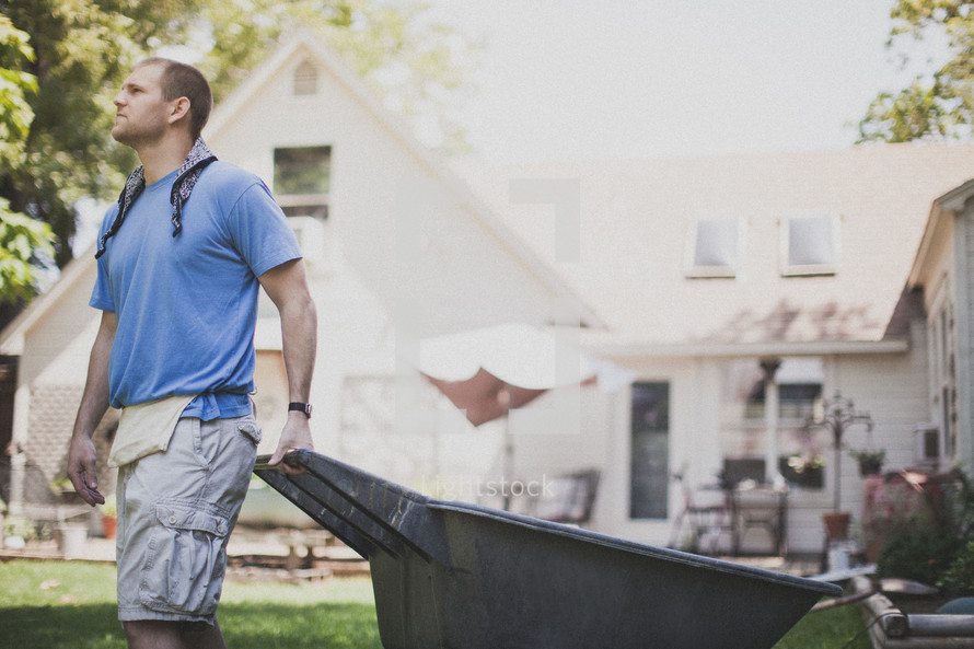 Man cleaning up after a service project using a wheel barrel