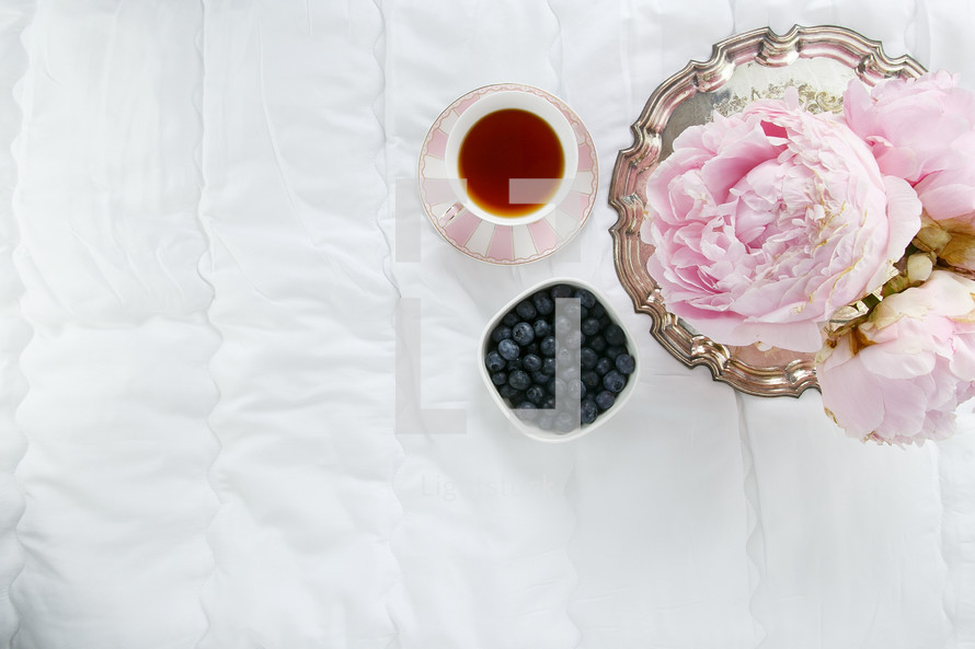 silver tray, cup of tea, bowl of blueberries, and peonies