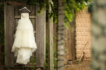 wedding dress hanging on a door outside