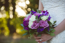 a bride holding a bouquet of purple roses