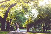 portrait of a bride and groom standing under a tree