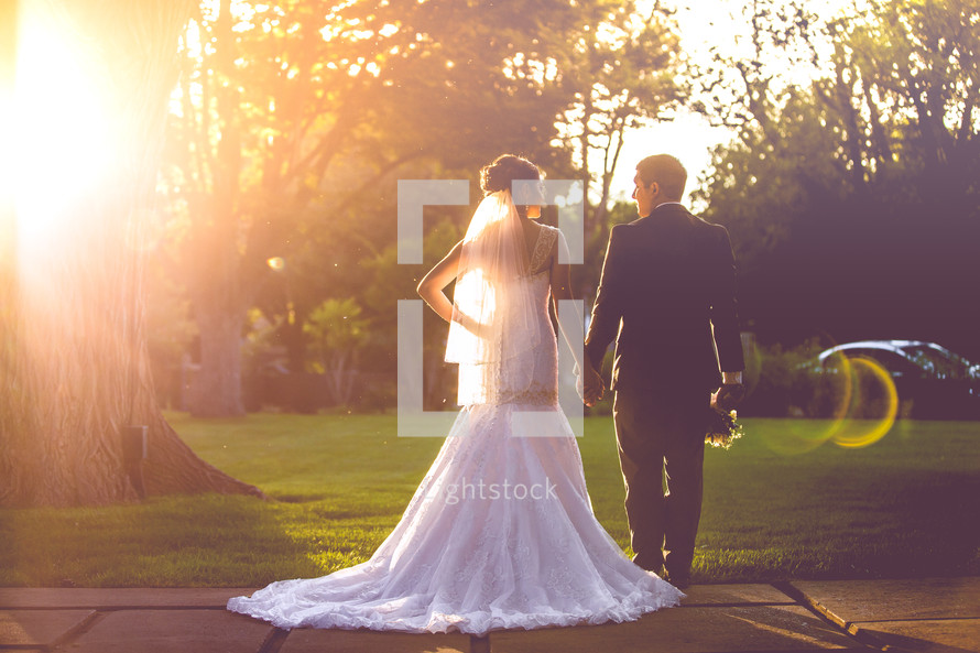 portrait of a bride and groom standing under bright sunlight