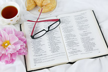 reading glasses, croissant, tea cup, open Bible, and pink flower