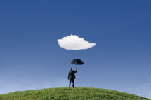 Businessman on a hill holding umbrella underneath a single cloud themes of anticipation protection out of context