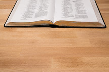 open pages of a Bible on a wood