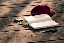 ball cap, journal, and pen on a deck