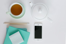 tea cup, tea pot, journal, notepad, pencil, and cellphone on white background