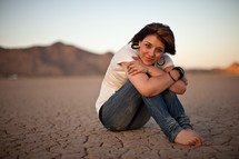 woman sitting on parched soil