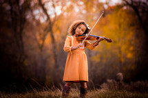 a girl playing a violin outdoors