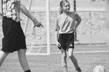 a girl on the soccer field and referee