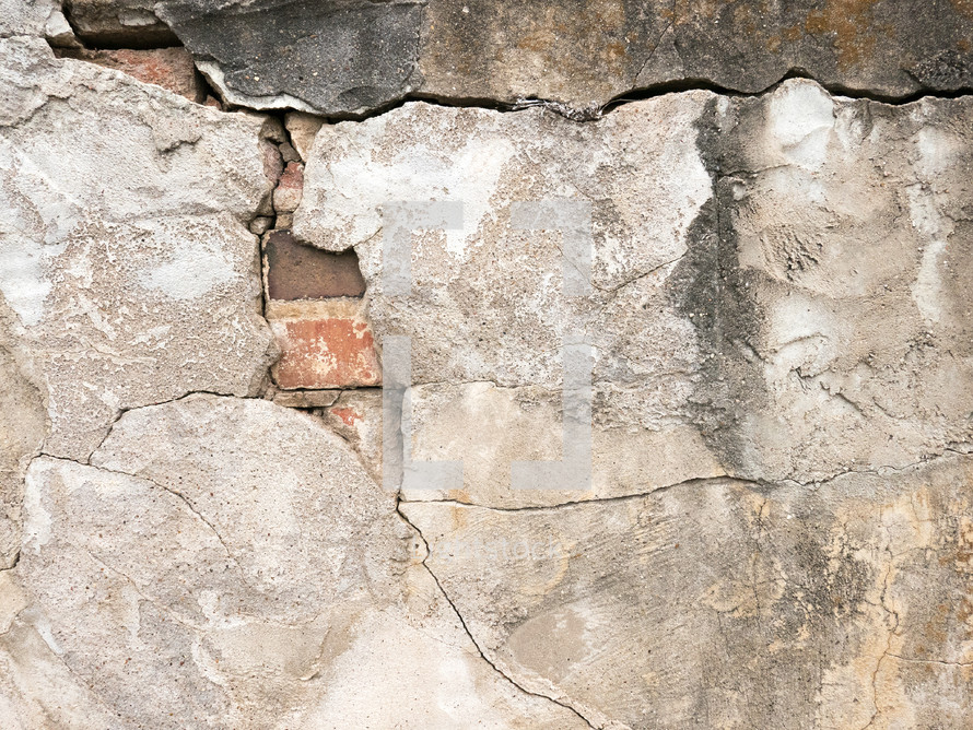 cracked wall surface revealing brick