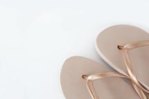 gold flip flops on pink