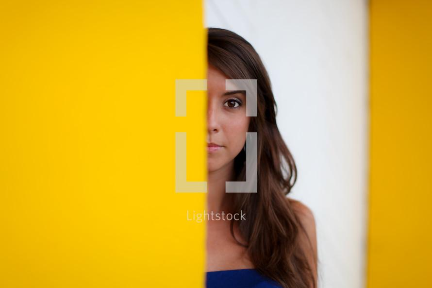 half of a woman's face peeking behind a yellow wall