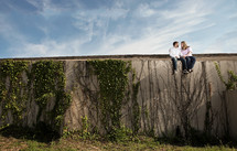 man and woman sitting on an ivy covered wall